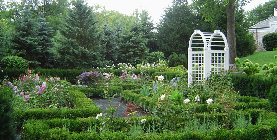 Formal boxwood parterre perennial garden rose arbor